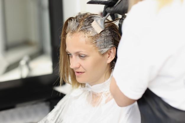 Jonge vrouw verft haar haar in de salon. professioneel werk van een kapper. veilige haarverf