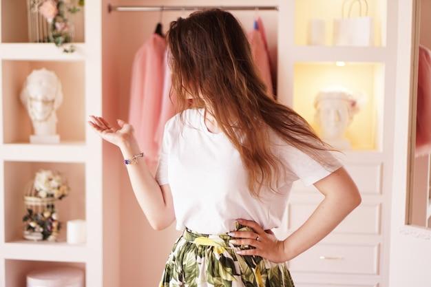 Jonge vrouw verkleden. kleedkamer in roze kleuren. het concept van mode en geluk