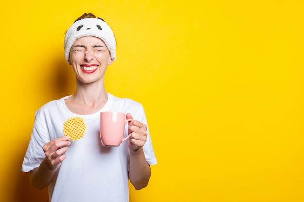 Jonge vrouw verknoeide haar ogen met een kopje koffie en een belgische wafel op een gele achtergrond