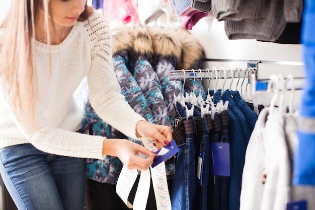 Jonge vrouw-verkoper lijmt de prijzen van de goederen - kinderkleding