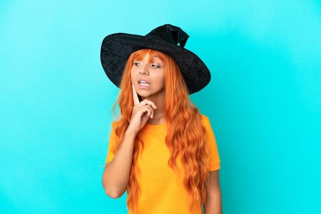 Jonge vrouw vermomd als heks geïsoleerd op blauwe achtergrond die een idee denkt terwijl ze omhoog kijkt