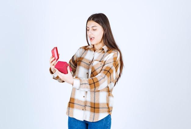 Jonge vrouw verrast over cadeau over witte muur.