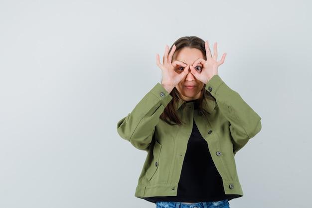 Jonge vrouw verrekijker gebaar in groene jas tonen en op zoek grappig. vooraanzicht.