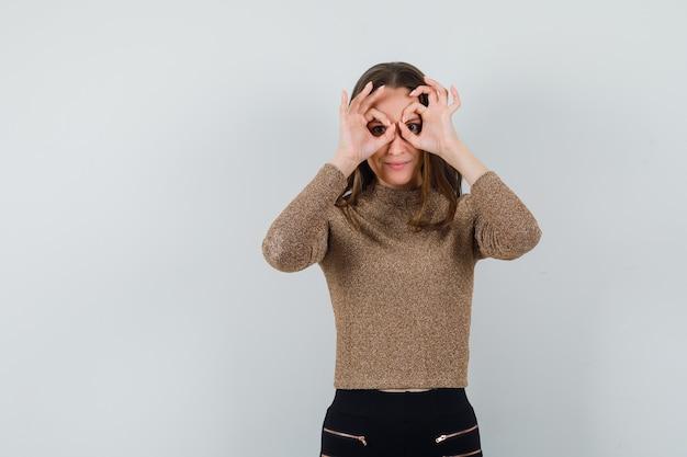 Jonge vrouw verrekijker gebaar maken op haar oog in gouden blouse en op zoek raar