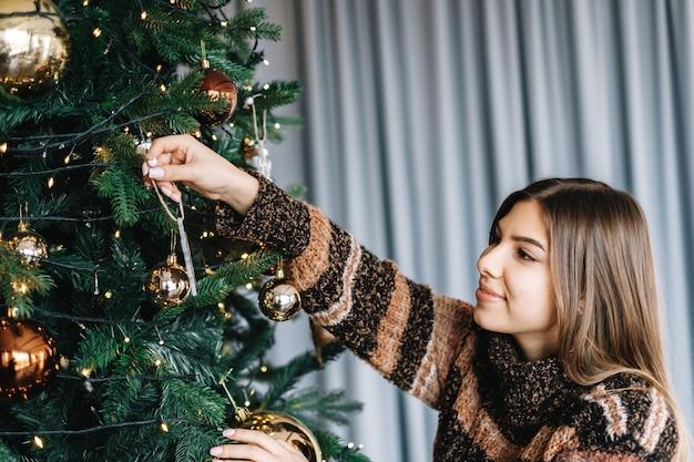 Jonge vrouw versiert de kerstboom met speelgoed. voorbereiding op de vakantie