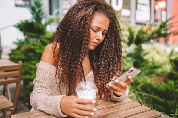 Jonge vrouw verslaafd aan technologie. vrouw gebruik smartphone achter café en drank drinken.