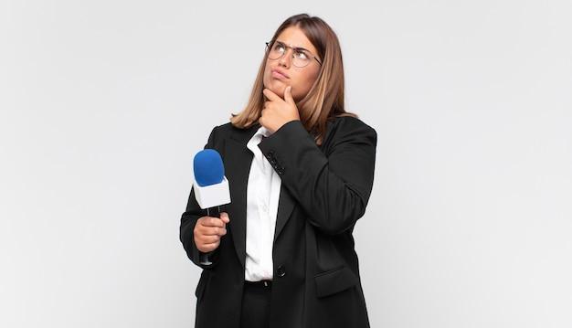 Jonge vrouw verslaggever denken, twijfelachtig en verward voelen, met verschillende opties, zich afvragend welke beslissing te nemen