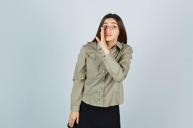 Jonge vrouw vertelt geheim achter hand in shirt, rok en kijkt nieuwsgierig, vooraanzicht.