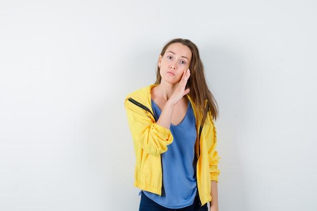 Jonge vrouw vertelt geheim achter hand in t-shirt, jas en kijkt bezorgd, vooraanzicht.