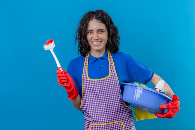 Jonge vrouw, vervelend, apron, en, rubberhandschoenen, vasthouden, bekken, met, poetsen, gereedschap, en, schrobborstel, met, grote glimlach, op, gezicht, positief, en, vrolijke, op, blauwe muur