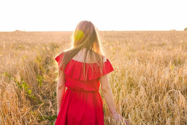 Jonge vrouw, vervelend, rode jurk, op, zomer veld, achteraanzicht