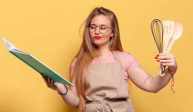 Jonge vrouw verward exssion chef kookconcept