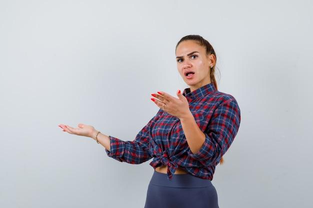 Jonge vrouw verwelkomt iets in geruit hemd, broek en kijkt verbaasd. vooraanzicht.