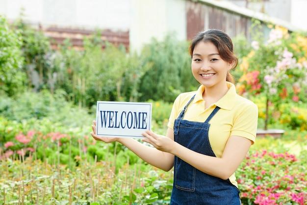 Jonge vrouw verwelkomt klanten