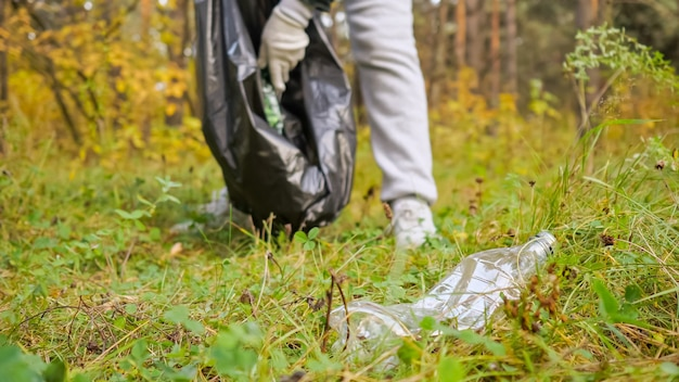 Jonge vrouw verzamelt afval in een zwarte verpakking in het bos