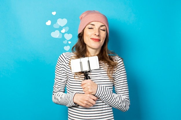 Jonge vrouw video blogger houdt de telefoon op een statief op een blauwe muur. het concept van verhaal, vlog, selfie, blog, verrassing, schok. banner.