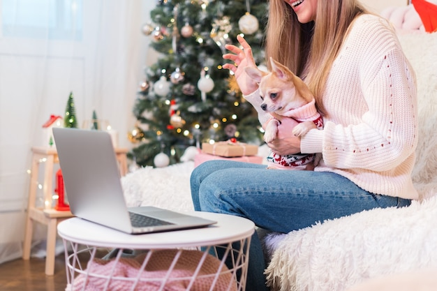Jonge vrouw video-oproepende familie om haar schattige hond te presenteren