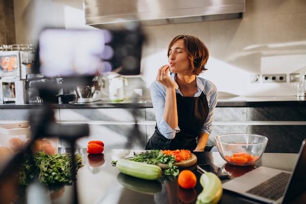 Jonge vrouw videoblogger koken in de keuken en filmen