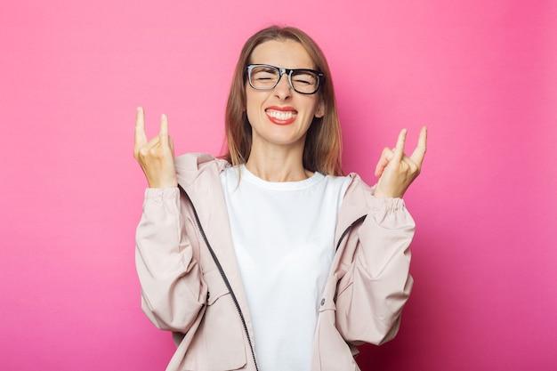 Jonge vrouw vieren en rock-'n-roll-gebaar in roze jasje, roze geïsoleerde achtergrond maken.