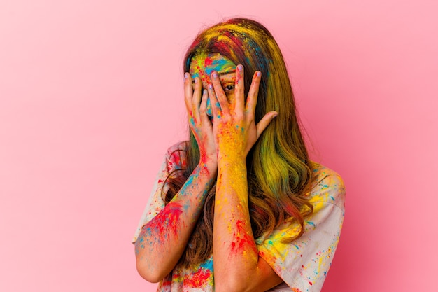 Jonge vrouw vieren heilig festival geïsoleerd op een witte muur knipperen door angstige en nerveuze vingers