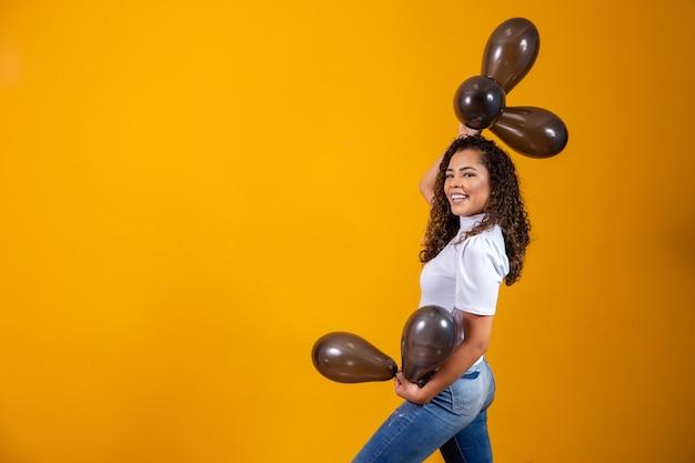 Jonge vrouw viert haar verjaardagsfeestje met een stelletje luchtballonnen.