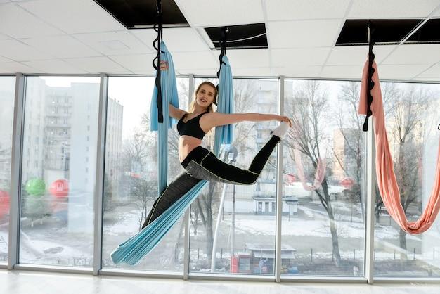 Jonge vrouw vlieg yoga oefeningen in de sportschool doet