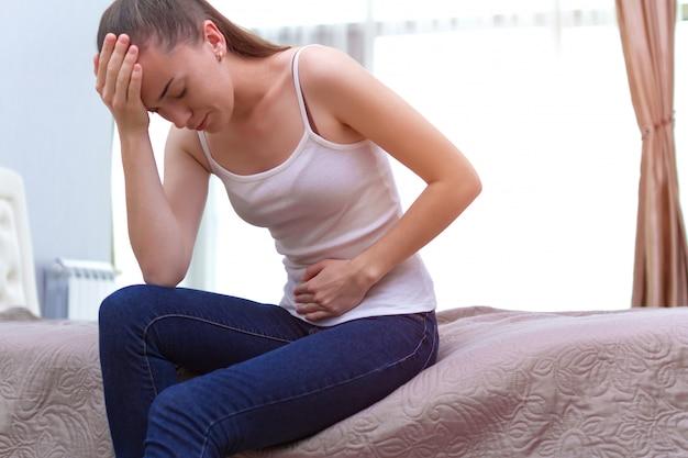 Jonge vrouw voelt buikpijn tijdens de menstruatie