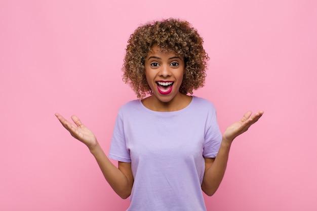 Jonge vrouw voelt zich gelukkig, opgewonden, verrast of geschokt, glimlachend en verbaasd over iets ongelooflijks over de roze muur