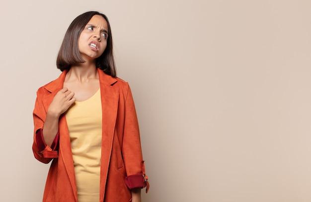 Jonge vrouw voelt zich gestrest, angstig, moe en gefrustreerd, trekt de hals van het shirt aan, kijkt gefrustreerd door het probleem