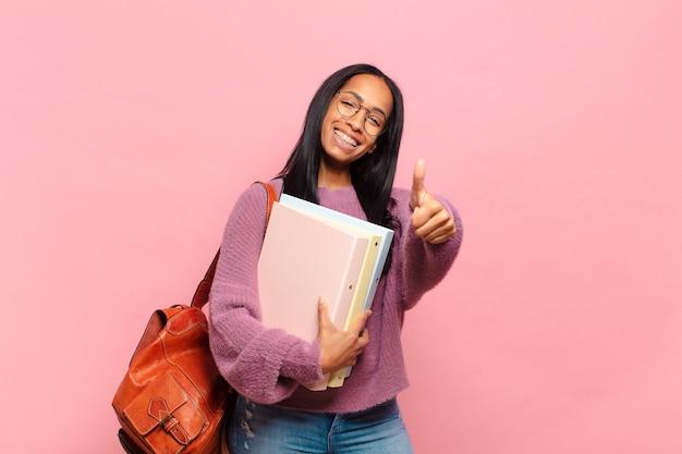 Jonge vrouw voelt zich trots, zorgeloos, zelfverzekerd en gelukkig, positief glimlachend met duimen omhoog