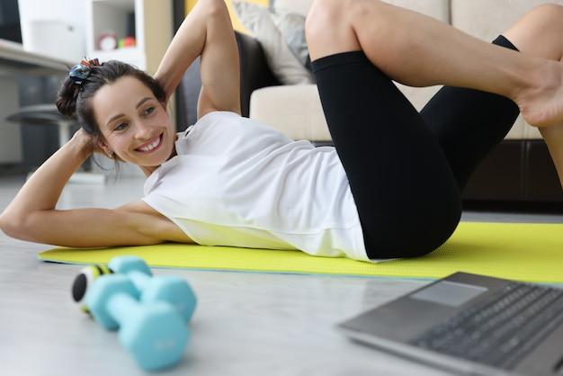 Jonge vrouw voert sportoefeningen uit voor buikdruk thuis op mat