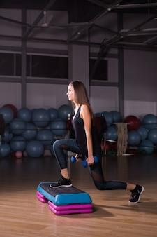 Jonge vrouw voert stap cardio met halters in een sportschool.