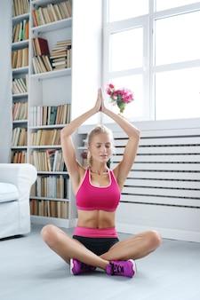 Jonge vrouw voert yoga bewegingen thuis uit