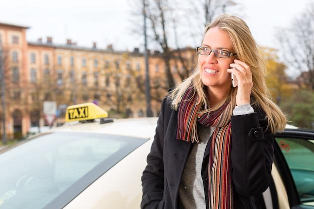 Jonge vrouw voor taxi met telefoon