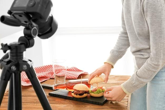 Jonge vrouw voorbereiding voor het fotograferen van voedsel binnenshuis