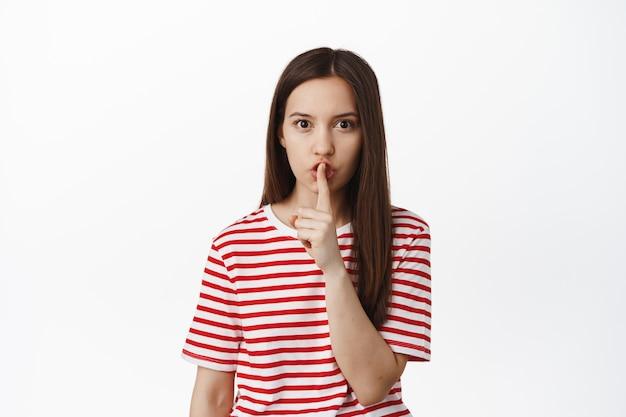 Jonge vrouw vraagt om stil te zijn, geheim te houden, sussend met vinger op lippen en fronsend, blijf stil, taboeteken, staande tegen witte muur.