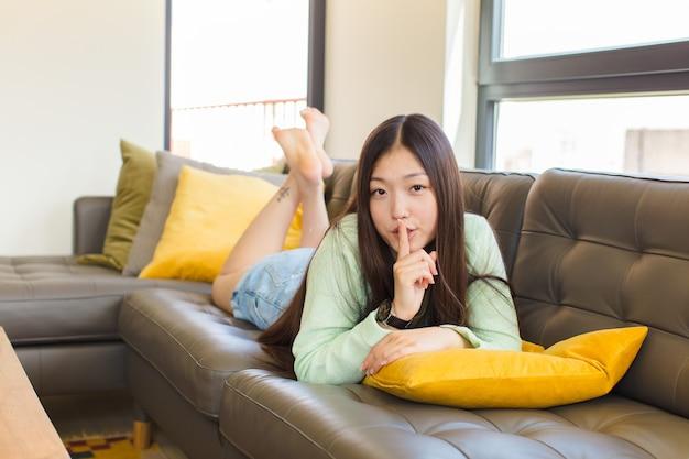 Jonge vrouw vraagt om stilte en stilte, gebarend met de vinger voor de mond