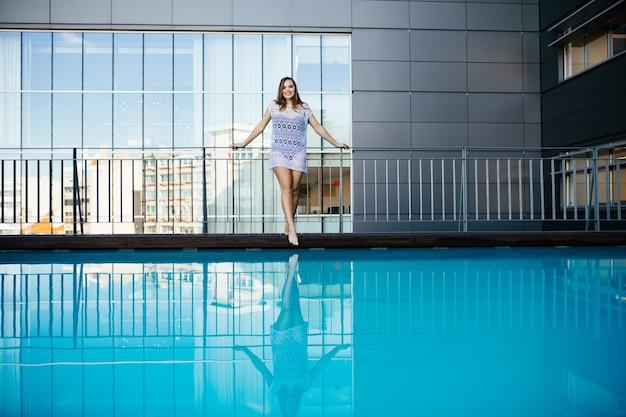 Jonge vrouw vrouw in prachtige kanten jurk naast zwembad op het dak