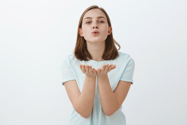 Jonge vrouw waait lucht kus met liefde en zorg