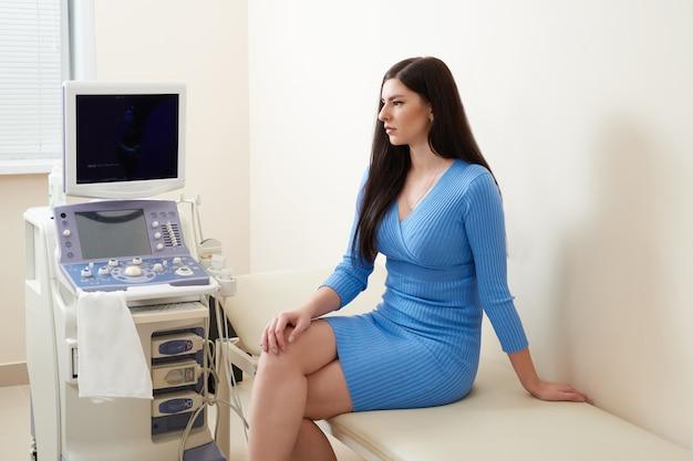 Jonge vrouw wachten op gynaecoloog om echografie te doen in medische kantoor