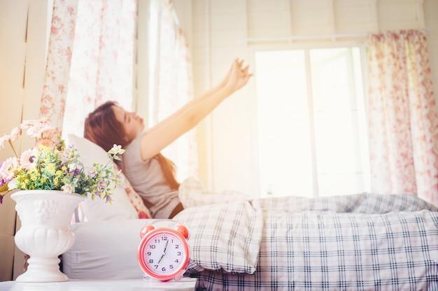 Jonge vrouw wakker stretch op het bed in de ochtend wekker ziet er zo fris dag