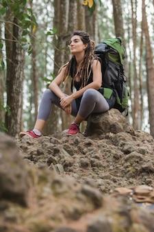 Jonge vrouw wandelaar ontspannen in het bos