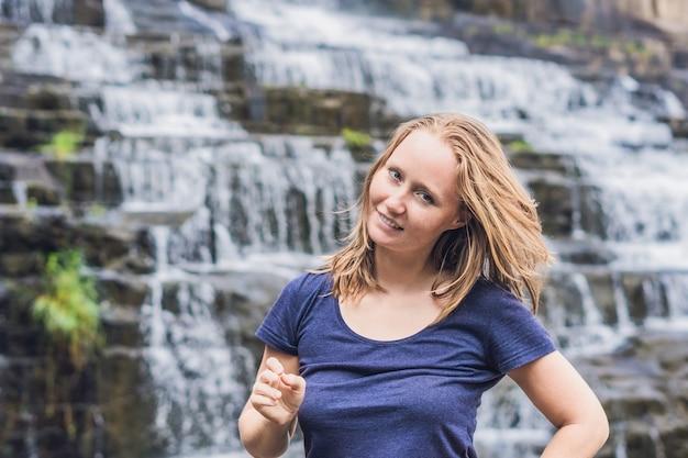 Jonge vrouw wandelaar, toerist op het oppervlak van amazing pongour waterfall is beroemd en mooiste van de herfst in vietnam