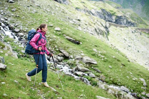 Jonge vrouw wandelen in de bergen met haar rugzak en wandelstokken