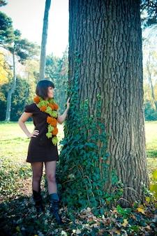 Jonge vrouw wandelen in herfst park gekleed in gebreide jurk.