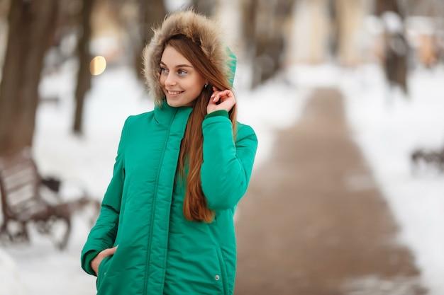 Jonge vrouw wandelen in het winterpark. winterpark in de sneeuw. kleding reclame foto concept.