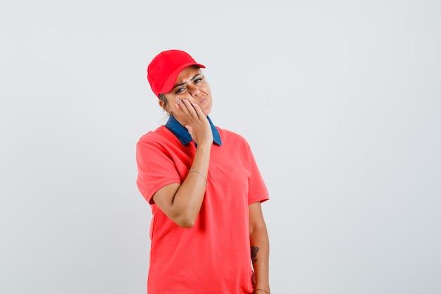Jonge vrouw wang leunend op palm, kiespijn in rood shirt en pet hebben en uitgeput kijken. vooraanzicht.