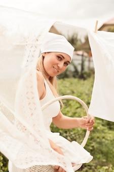 Jonge vrouw wasgoed buiten ophangen
