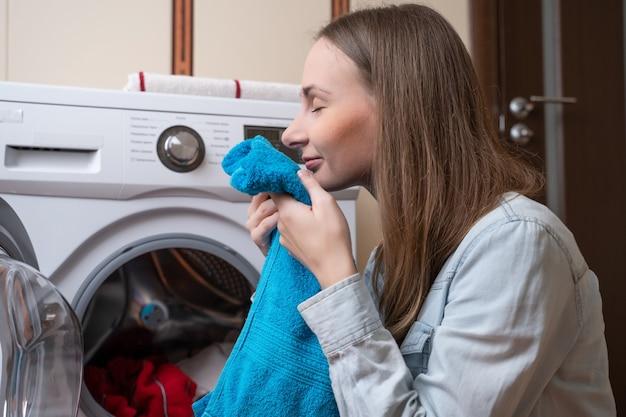 Jonge vrouw wasserij ingebruikneming wasmachine vrouw wassen wasgoed met behulp van moderne automatische machine