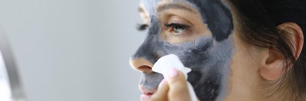 Jonge vrouw wast zwarte kleimasker weg van gezichtsportret. home gezichtsbehandelingen concept.